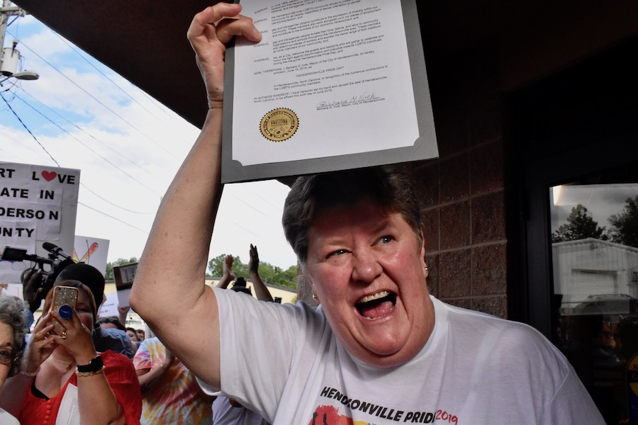 Laura Bannister celebrates as she holds proclamation.