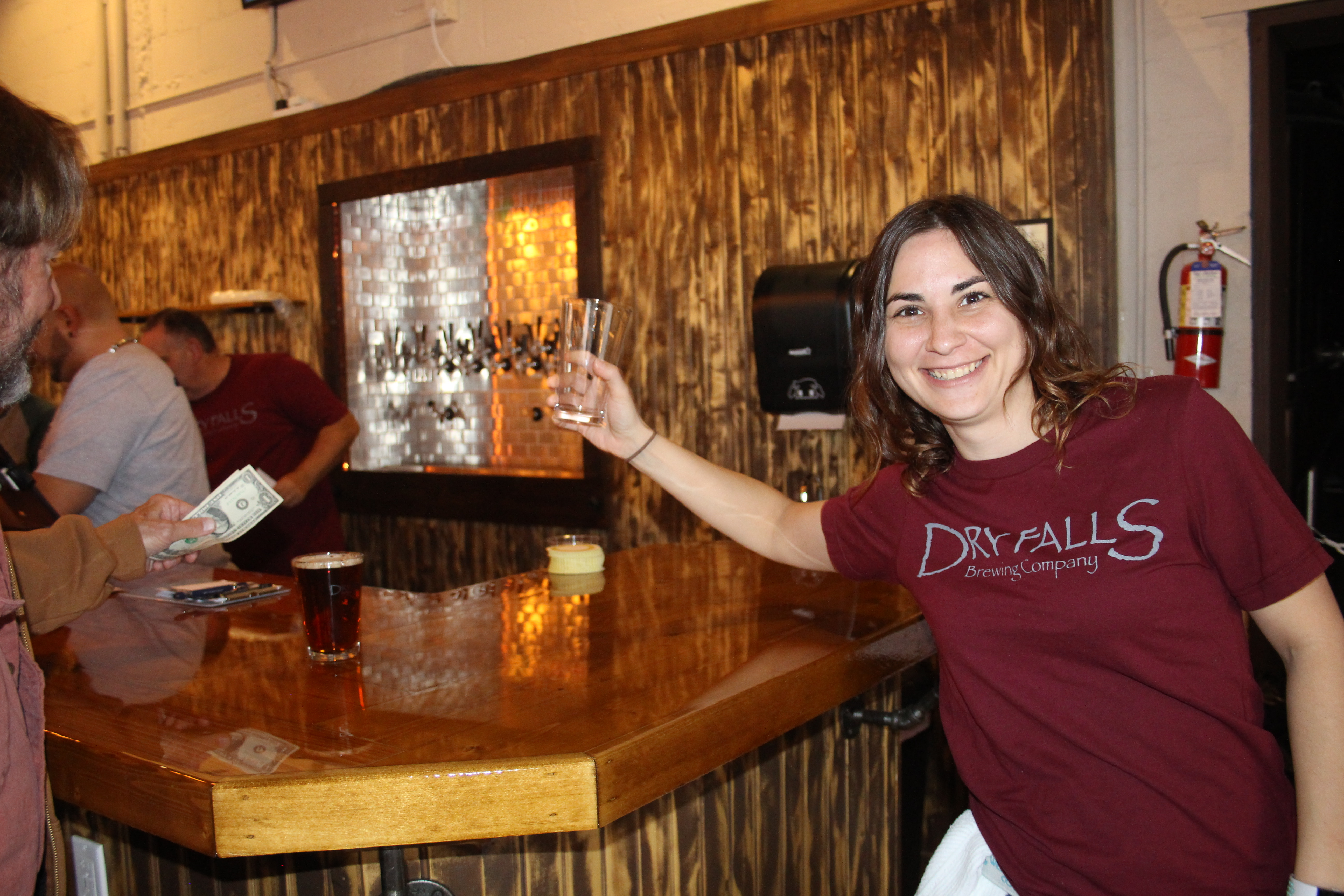 A server celebrates on opening day at Dry Falls Brewing Co.