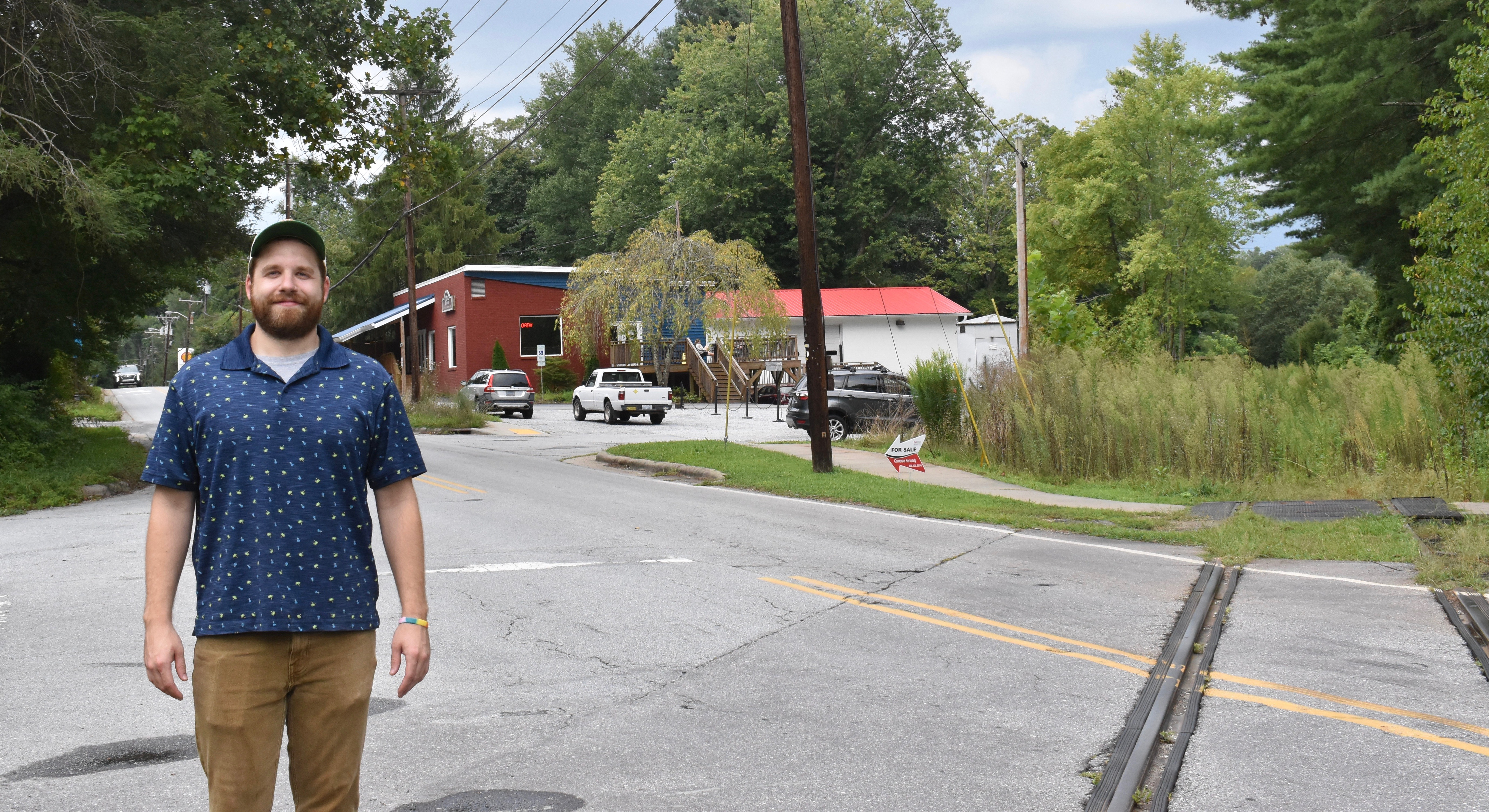 Appalachian Coffee Co. manager Zach Pickett stands on railroad tracks that could become the Ecusta Trail.