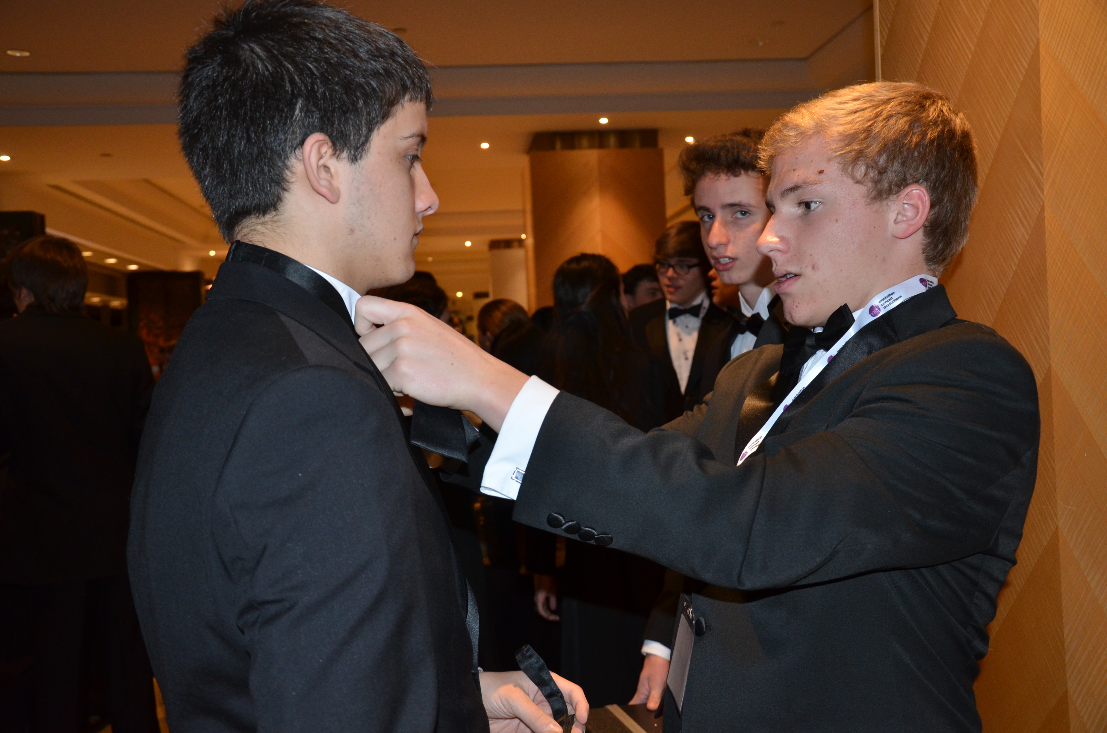 Drew Eudy adjusts the tie of Seth Alexander before the performance at Carnegie Hall [PHOTO BY ROBIN REED]