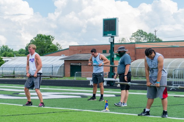 Coach Daniel Corhn looks on as East Henderson Eagles Billy Johnson, Ty McCrary and Donaven McHenry lift weights, six feet apart.