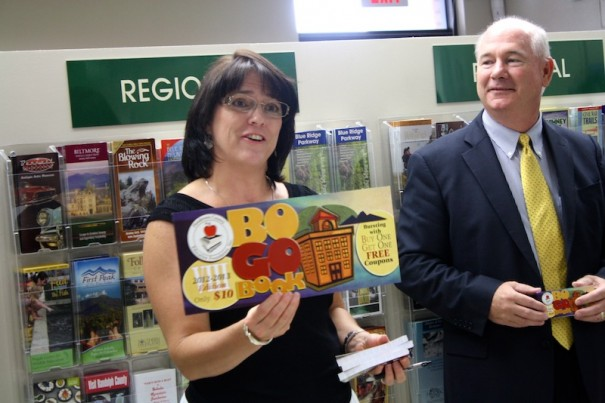 Donna Robinson, of Robinson & Associates, displays the 2012-13 BOGO book as schools superintendent David Jones looks on.