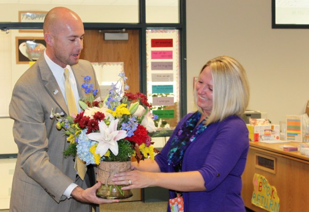 Human Resources Director John Bryant surprises Sugarloaf Elementary School principal Peggy Marshall with a bouquet of flowers.