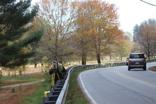 A surveyor takes measurements on Highland Lake Road, where the NCDOT plans widening work with a greenway.