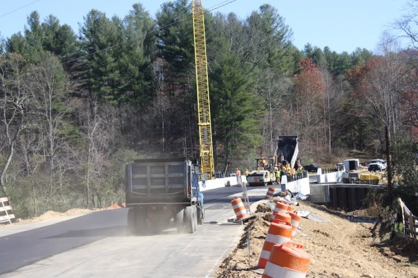 Crews work on paving the roadway of the new bridge over Mud Creek on Little River Road in Flat Rock.