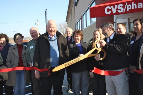 Hendersonville Mayor Pro Tem Ron Stephens and Chamber of Commerce members look on as store manager Bruce Gatta cuts the ribbon for the new CVS store on South Main Street.