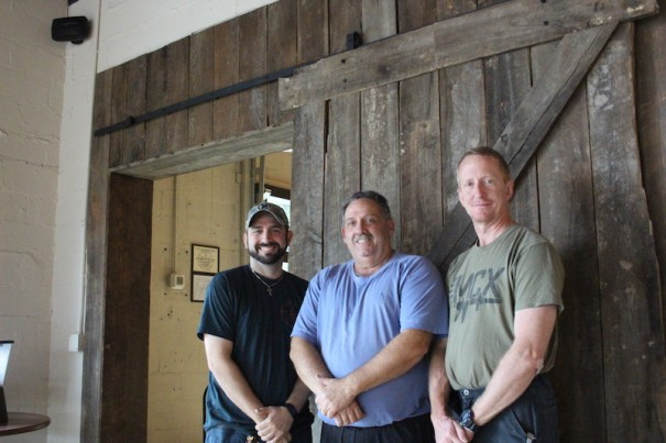 Evan and Jeff Golliher and brewer John Duncan stand in front of a wooden sliding door at Dry Falls Brewing Co., which is expected to open in the coming days on Busy Bend.