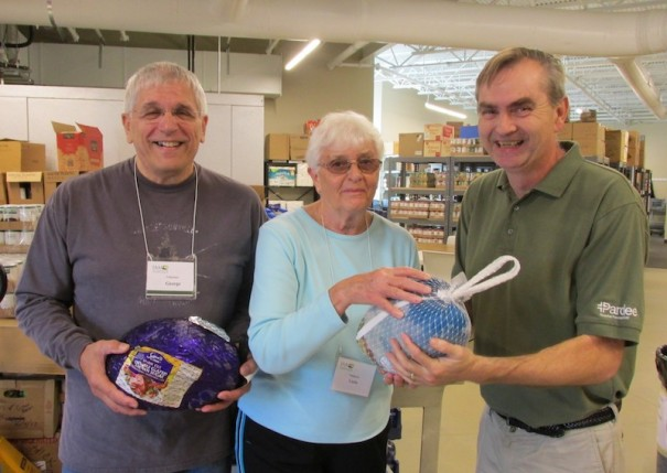 IAM food pantry manager Ernest Brown, right, accepts a turkey from volunteers George and Linda in 2019. [LIGHTNING FILE PHOTO]