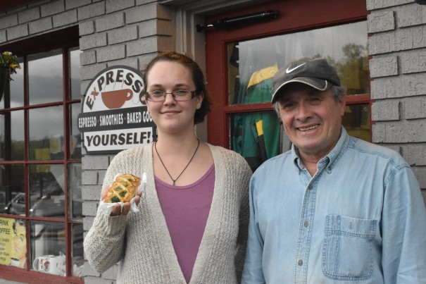 Barista Lauren Rowe, with Expresso Yourself owner David Hamilton, shows off a spinach and cheese croissant.