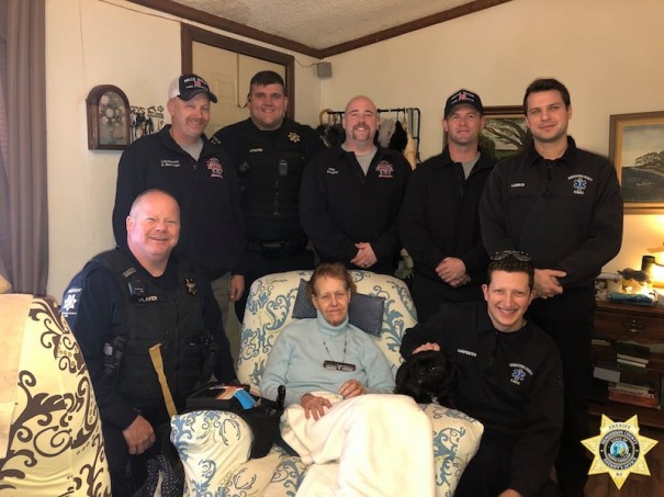 Sheriff's deputies, EMS personnel and Mills River firefighters pose with Laura Brown. The first responders quick action saved Brown and her two dogs and limited damage when a kitchen fire broke out.
