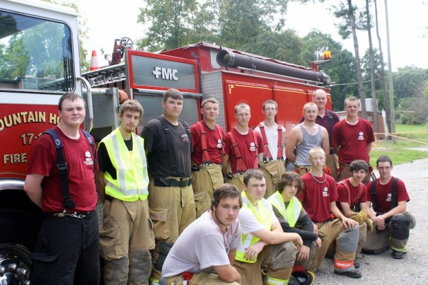 Students at Balfour's fire academy pose in front of a fire engine.