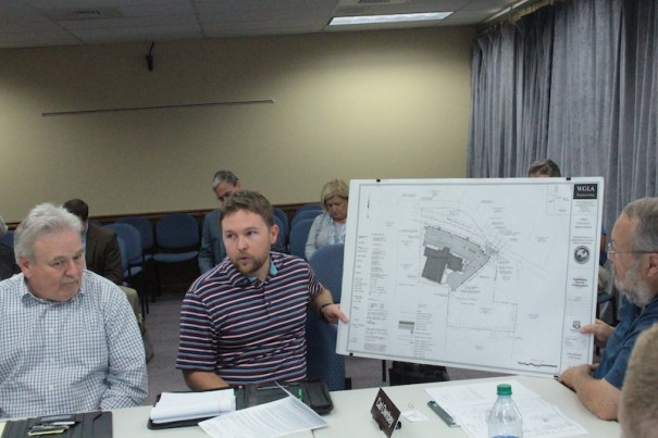Engineer Jared DeRidder (center) shows drawing of proposed Residential Recovery Center as First Contact President Craig Halford (left) looks on.