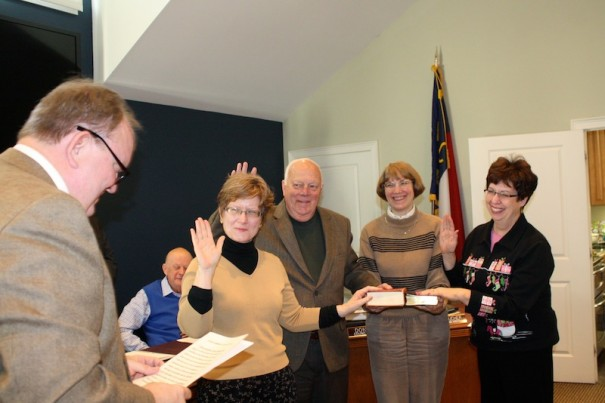 Anne Coletta, Albert Gooch and Sheryl Jamerson (right) repeat the oath of office from state Rep. Chuck McGrady as Connie Backlund holds Bibles.