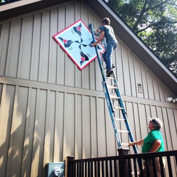 Gary Steiner hangs the new quilt block designed by Georgia Bonesteel at the Welcome Center at The Park at Flat Rock.