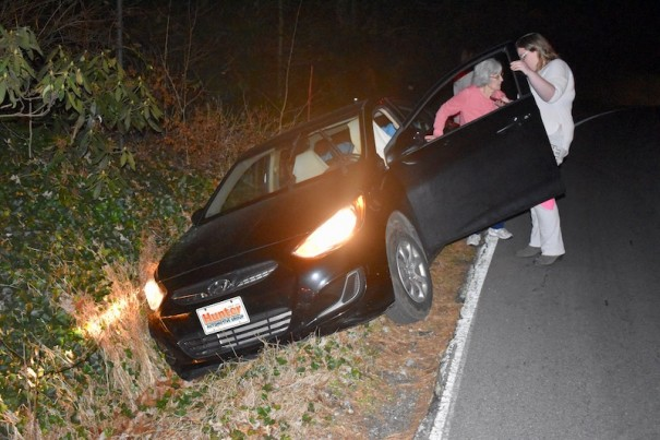 An elderly driver stands beside her car after driving off Highland Lake Road around 9 p.m. Monday, Dec. 16.