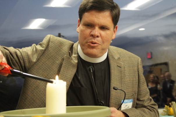 The Rev. Tom Jones of the Hendersonville Rescue Mission lights a candle to signify the blessing of IAM's service to the poor.