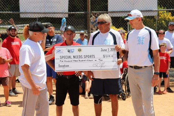 Sheriff's Office Maj. Frank Stout and senior softball players Don Ward and Sonny Johnston present a check to Special Needs Sports leader Donnie Jones (in red shirt).