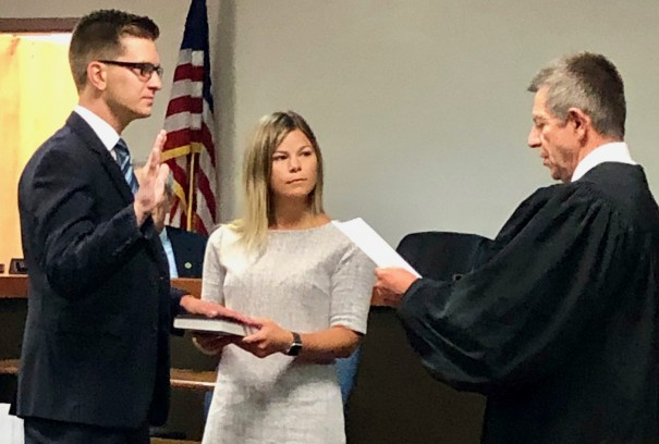 Superior Court Judge Peter Knight administers the oath of office as Jake Johnson becomes a state representative. Holding the Bible is Johnson's girlfriend Liz Driver.