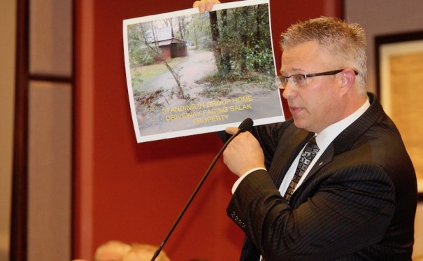 Mark Salak, of 219 Erkwood Drive, points to a photo of flooding around his property, which he said could worsen with more development.