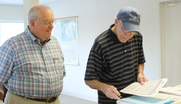 Flat Rock Mayor Bob Staton looks on as Fletcher Councilman Bob Davy studies filing forms.