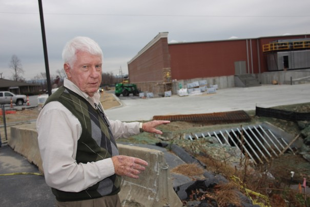 Jim Barnett points to a grill at the opening of a culvert. A logjam could create a dam in a heavy rainstorm, Barnett says.
