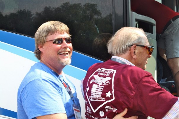 Jim Miller, a Hendersonville grading contractor, helps a World War II veteran board a bus during an HonorAir trip in September 2013.