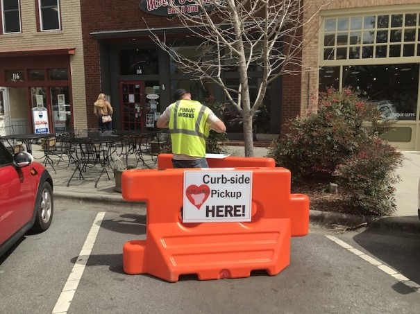 City public works employee Jody Martin places barrier to reserve parking spaces in front of Moe's barbecue.