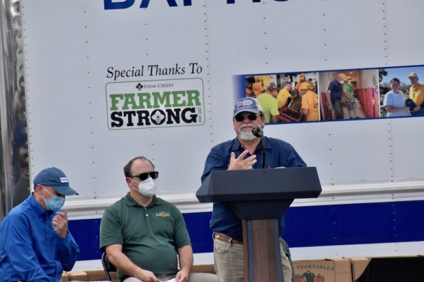 Kirby Johnson, right, hosted apple farmer Kenny Barnwell (left) and U.S. Agriculture Secretary Sonny Perdue on a July 27 visit that showcased the USDA's Farmers to Families Food Box Program. [LIGHTNING FILE PHOTO]