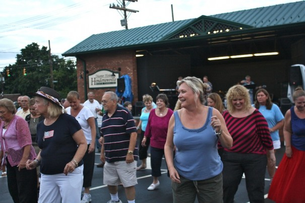 Line dancers enjoy the music of Sound Investment at Music on Main Friday night.