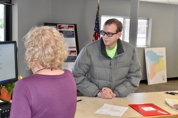 Elections Director Karen Hebb helps School Board member Michael Absher file for re-election on Monday.