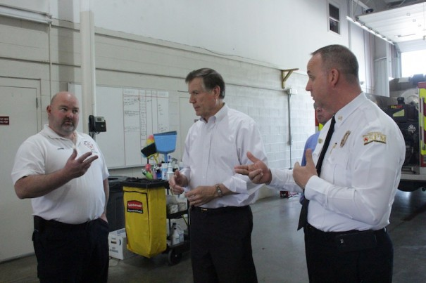 Edneyville Fire Chief Robert Griffin, Insurance Commissioner Mike Causey and Brian Taylor, of the state's fire marshal's office, talk about turnout gear.