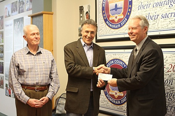 Jeff Miller presents an HonorAir check to Scott Rogers (right) as county Veterans Affairs Director Mike Murdock looks on.