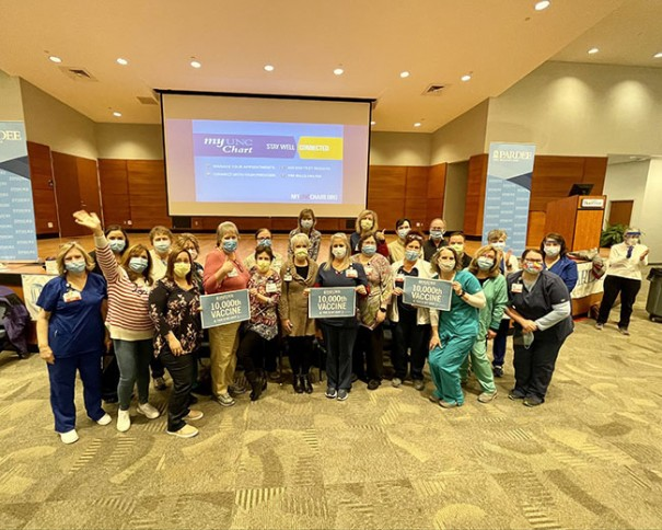 Volunteers and staff celebrate 10,000 dose at Pardee Vacinne Clinic on Saturday.
