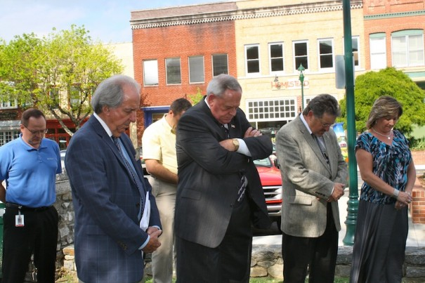 Larry Rogers, of the PEP business organization, County Commissioners Larry Young and Charlie Messer, and board clerk Terry Wilson pray outside before a meeting in May 2012.