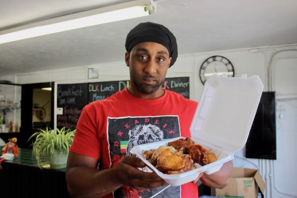 Raynard Walker serves a plate of fried and smoked wings at his Dread Life Kitchen.