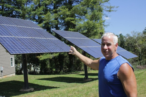 Keith Metler points to solar panels that supply the power for his 2,400-square-foot home.