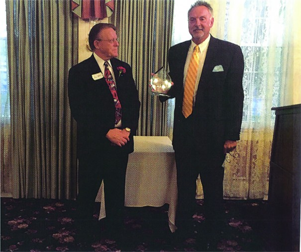Emcee Don Holder presents construction company owner Tom Cooper with the Clifton J. Shipman Community Service Award last week at the Hendersonville Merchants and Business Association