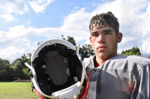 Alex Lemmens, a junior linebacker for the HHS Bearcats, shows the helmet he wears equipped with a sensor to measure the impact of hits.