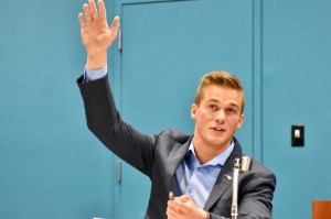 Madison Cawthorn raises his hand in support of allowing the media to stay at a forum after 11th District Chair Aubrey Woodard asked two reporters to leave.
